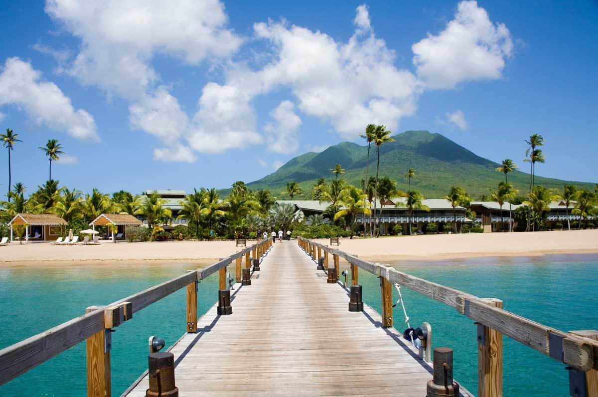 Stunning Pinney's beach with Coconut Palms, and the Volcano in the distance, at Nevis. Caribbean